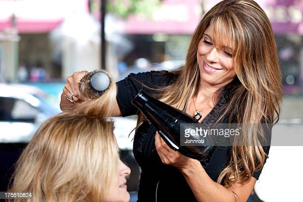 Hairdresser working  blowing out hair in salon, smiling
