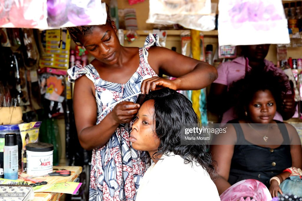 A hairdresser works in her store inside the market of Mbalmayo (village south Yaounde) on February 18, 2018 in Yaounde, Cameroon. Cameroon is often referred to as 'Africa in miniature' for its geological and cultural diversity. Natural features include beaches, deserts, mountains, rainforests, and savannas.