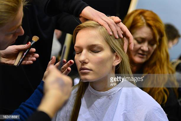 Hairdressers and makeup artists work on a model backstage prior the Trussardi FallWinter 20132014 Womenswear collection on February 23 2013 during...