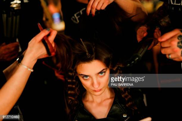 TOPSHOT Hairdressers brush a model´s hair during the 080 Barcelona Fashion Week in Barcelona on January 31 2018 / AFP PHOTO / PAU BARRENA