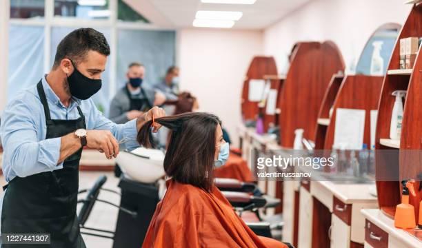 coiffeurs coupant les cheveux, pendant covid-19 - salon de coiffure photos et images de collection