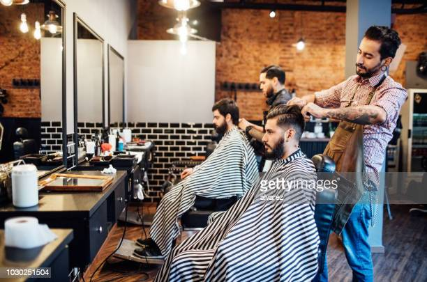 hairdressers cutting hair of clients in salon - barber shop stock photos and pictures