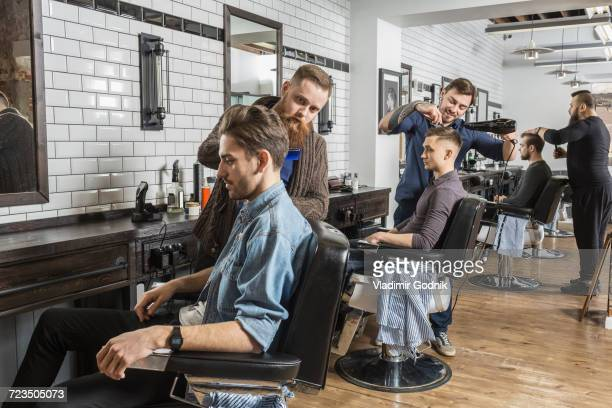 hairdressers cutting male customers hair in salon - friseurberuf stock-fotos und bilder