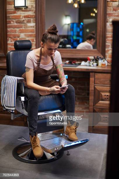 hairdressers in barber shop texting on smartphone - 美容室 椅子 ストックフォトと画像