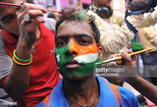 Hairdressers paint Indian and Pakistani national flags on the face of a cricket fan ahead of the Cricket World Cup opening ceremony in Mumbai on...