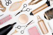 Hairdressing tools and various hairbrushes on white background top view