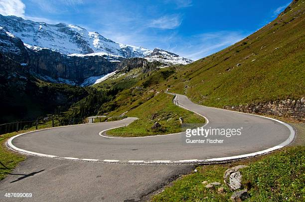 hairpin curve, mountain road to the klausen pass in front of the glarus alps, urnerboden, canton of uri, switzerland - hairpin curve stock photos and pictures