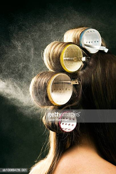 Hairspray being sprayed on woman's hair on curlers