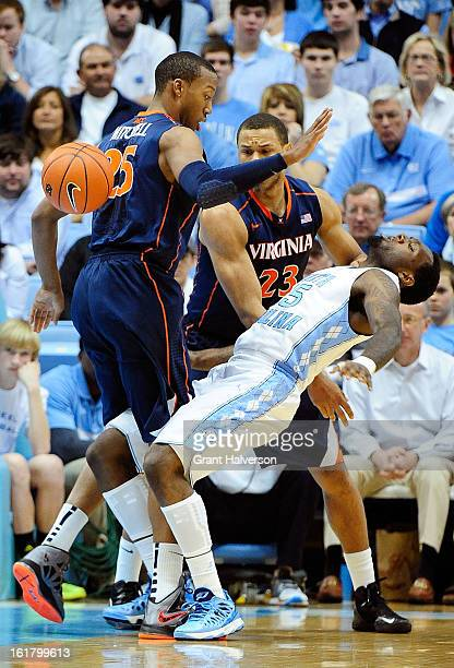 J Hairston of the North Carolina Tar Heels loses the ball as he collides with Akil Mitchell of the Virginia Cavaliers during play at the Dean Smith...