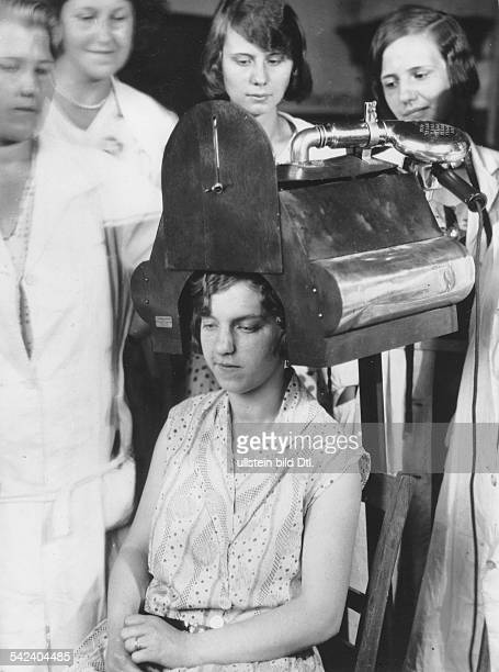 Hairstyle Water based perms are dried under a drying hood like demonstrated in a hairdresser's school 1930 Vintage property of ullstein bild