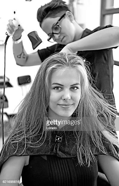 Hairstylist blowdrying a young beautiful female customer's hair