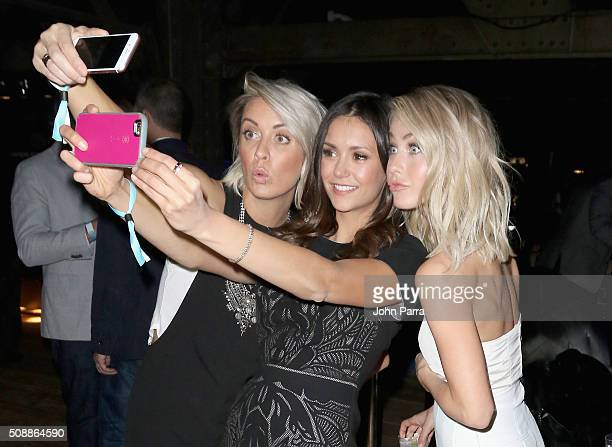 Hairstylist Riawna Capri actresses Nina Dobrev and Julianne Hough pose for a selfie photo at the DirecTV and Pepsi Super Saturday Night featuring Red...