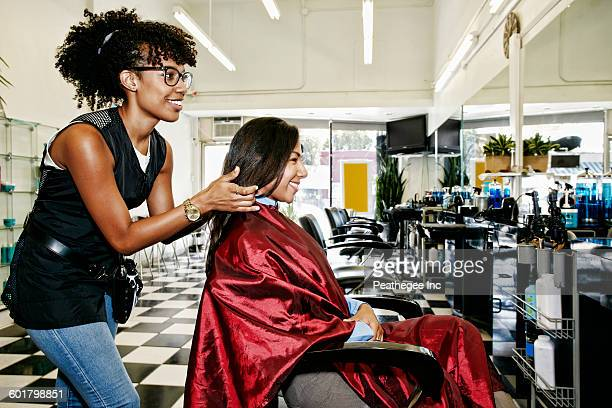 Hairstylist styling hair of customer in salon