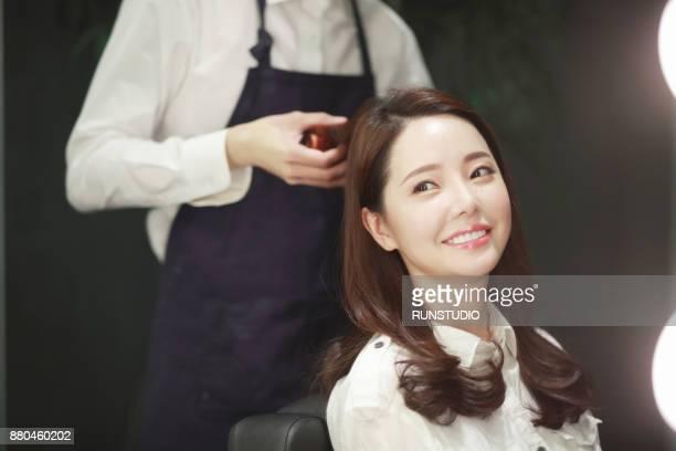 hairstylist styling hair of customer in salon - koreanischer abstammung stock-fotos und bilder