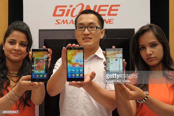 Hairui Sun manager with Chinese smartphone maker Gionee poses with models holding Gionee Elife E7 handsets during an event launch in Amritsar on...