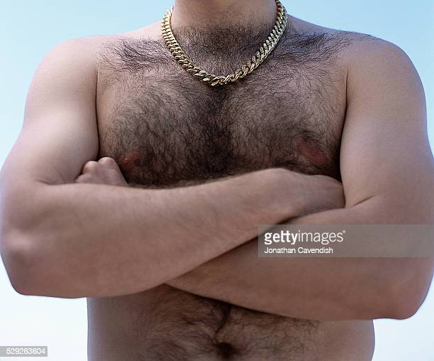 hairy chested man with gold chain and arms crossed - hairy man chest stock photos and pictures