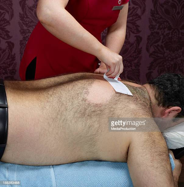 hairy male back waxing - hairy man stock photos and pictures