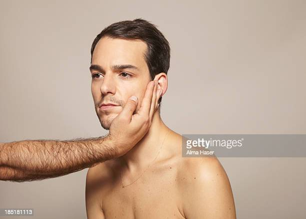 Hairy man's arm holding another mans face