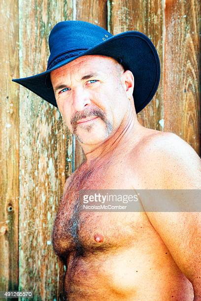 hairy shirtless mature cowboy against wooden fence - hairy chest stockfoto's en -beelden