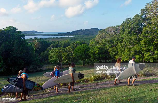 Haiti, Sud, Ile a Vache, surfers walking with surfboards in Cacor district.