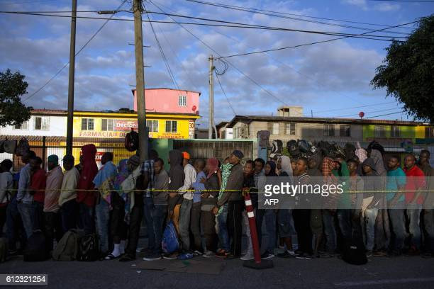 TOPSHOT Haitian and African migrants seeking for asylum in the United States line up outside a Mexican Migration office on October 3 in Tijuana...