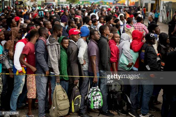 Haitian and African migrants seeking for asylum in the United States line up outside a Mexican Migration office on October 3 in Tijuana northwestern...