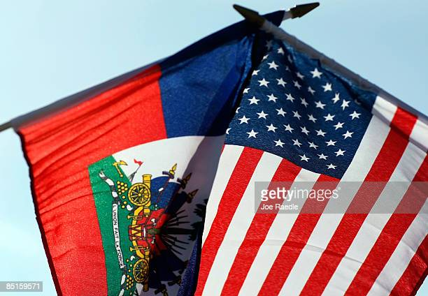 Haitian and American flags are held together during a demonstration in front of the Broward Transitional Center to urge the United States government...