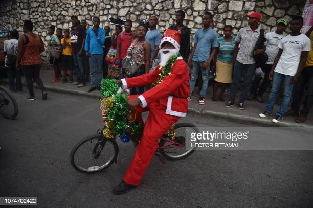 A Haitian boy dressed in a Santa Claus costume participates in a Christmas Parade on the streets of the commune of Petion Ville in the Haitian...
