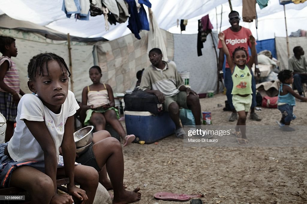 Haitian child and their relatives are seen in their tent at a temporary camp in the Juvena Park on January 30, 2010 in Port Au Prince, Haiti. As many as 200,000 people died on January 12 as a consequence of the 7.0-magnitude earthquake. At least 130 people have been pulled alive from the rubble. An estimated 1.5 million people have been left homeless. The Haitian government is planning to relocate some 400,000 people, currently in makeshift camps across the capital, to temporary tent villages outside the city. Aid agencies are still struggling to supply food and water to survivors, while thousands of Haitians who suffered serious injuries remain in need of urgent medical attention.