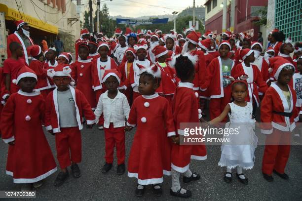 Haitian Children in Santa Claus costumes participate in a Christmas Parade on the streets of the commune of Petion Ville in the Haitian capital...