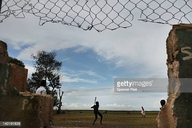 Haitian children play baseball on a batey on February 29, 2012 in San Pedro, Dominican Republic. A batey is the name given to communities that reside...
