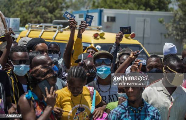 Haitian citizens hold up passports as they gather in front of the US Embassy in Tabarre, Haiti on July 10 asking for asylum after the assassination...