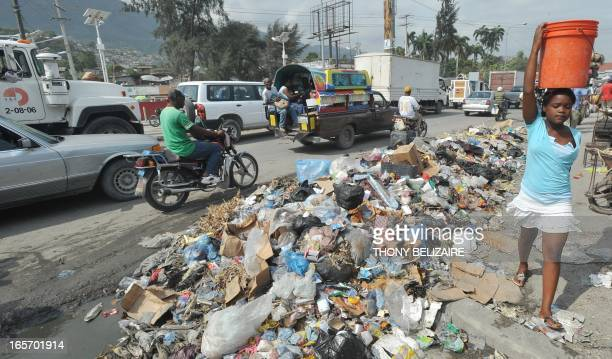 Haitian commuters pass trash dumped on a street in the PortauPrince neighborhood of Martissant on April 5 2013 The Haitian Human Rights Organizations...
