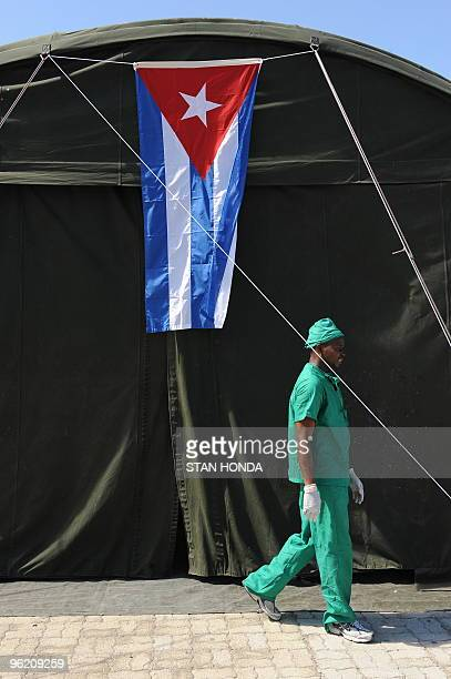 A Haitian doctor walks past the operating room tent with a Cuban flag on January 27 2010 at a medical clinic set up by a group of Cuban doctors in...