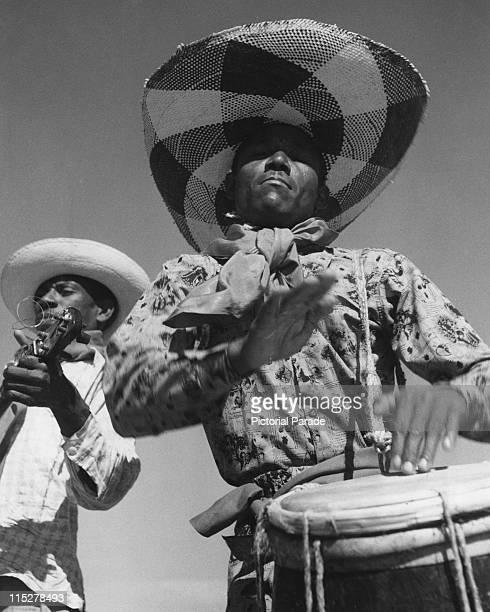 Haitian drummer, wearing a wide-brimmed hat while beating a drum with his hands, with a man behind him playing a stringed instrument, in...
