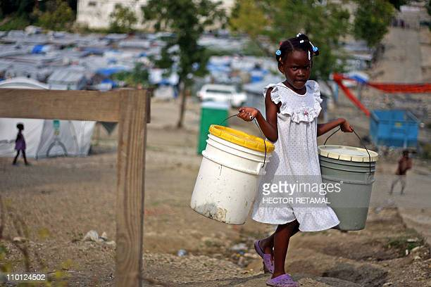 A Haitian girl carries plastic buckets to collect water in the camp Acra Delmas January 9 2011 in PortauPrince On January 12 Haiti commemorates the...