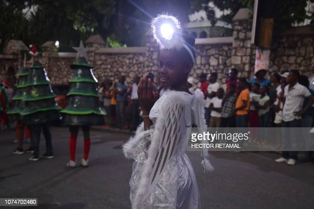 A Haitian girl dressed in an angel costume participates in a Christmas Parade on the streets of the commune of Petion Ville in the Haitian capital...