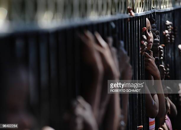 A Haitian girl living in a makeshift camp at a park looks through the bars of the park at a memorial service held in front of the collapsed Ministry...