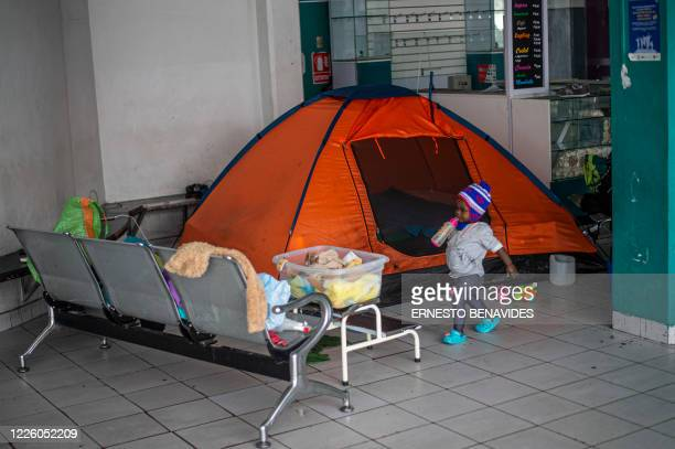 A Haitian girl walks next to a tent installed at a bus station in Lima on July 10 2020 On March 16 2020 the order of compulsory national confinement...