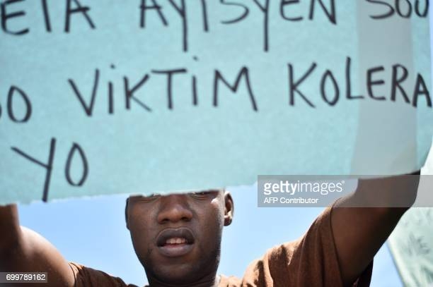 Haitian human rights activists and victims of cholera in Haiti protest in front of the Log Base of Minustah in PortauPrince on June 22 to demand...