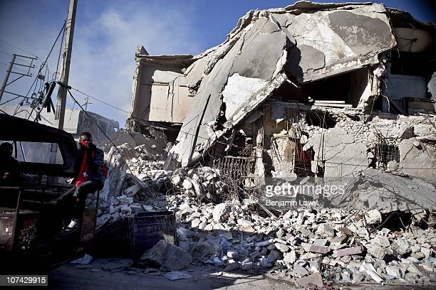 Haitian man covers his face as he is driven past a destroyed building in downtown Port au Prince. On January 12, 2010 Haiti was struck by a magnitude...