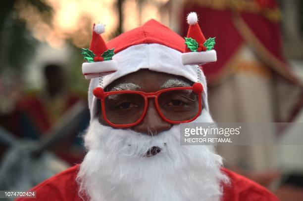 Haitian man in a Santa Claus costume participates in a Christmas Parade on the streets of the commune of Petion Ville in the Haitian capital...