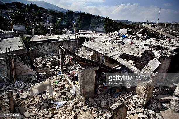 Haitian man scavenges for clothing and his other belongings in the collapsed remains of his house in the Dante's Viullage neighborhood in Port au...