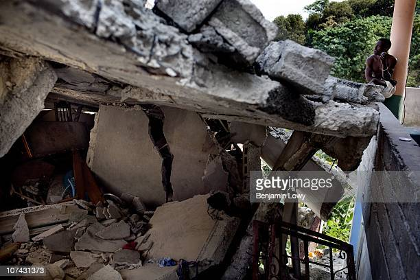 Haitian man sits on his porch neighboring the remains of several collapsed buildings in the Dante's Viullage neighborhood in Port au Prince on...