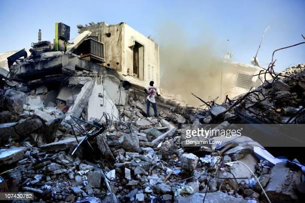 Haitian man stands amongst the debris of earthquake ravaged downtown Port au Prince, Haiti. On January 12, 2010 Haiti was struck by a magnitude 7...