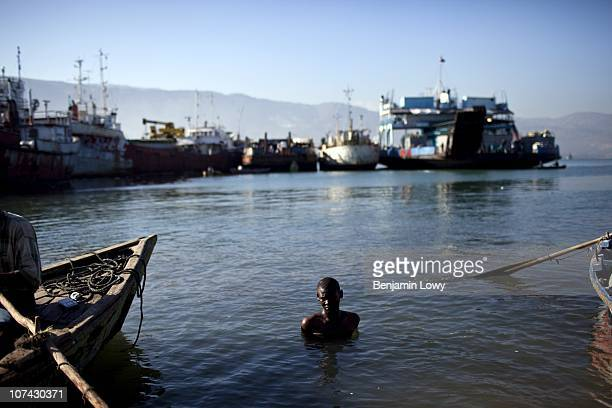 Haitian man swims in the water along Port Jeremie, the departure point for boats heading to the southern rural city of Jeremie. Hundreds of Haitian...