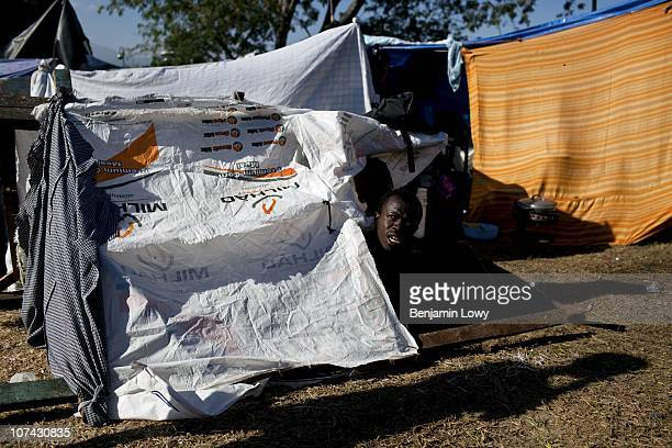 Haitian man wakes in a small tent made of tarps and sheets in the Champs des Mars IDP camp in Port au Prince on February 2 2010. Haiti was struck by...