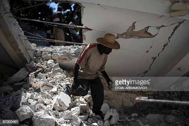 A Haitian man walks before a fallen wall of a building adjacent to the devastated main church of the coastal city of Leogane on February 23 2010 The...