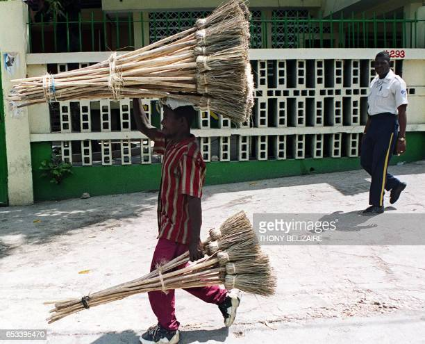 A Haitian man walks down a PortauPrince street 15 May 2000 carrying bundles of home made brooms for sale Haitians are preparing for national...