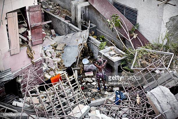 Haitian man washes himself in an alleyway between two destroyed homes in the hard hit Carrefour Feuilles neighborhood of Port au Prince Haiti on...
